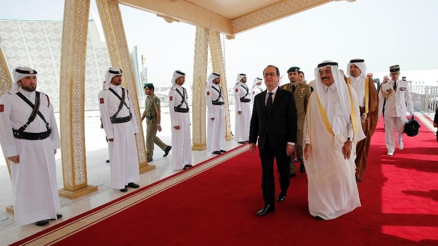 French President Francois Hollande, center,  is greeted by Culture minister of Qatar Dr. Hamad Bin Abdulaziz Al-Kuwari at the Doha airport, Qatar, Monday, May 4, 2015. Hollande is seeking to solidify strategic alliances in the Persian Gulf, as he heads to Qatar to sign a 7-billion-euro fighter jet deal and then gets a starring role in a regional summit in Saudi Arabia. (AP Photo/Christophe Ena, Pool)