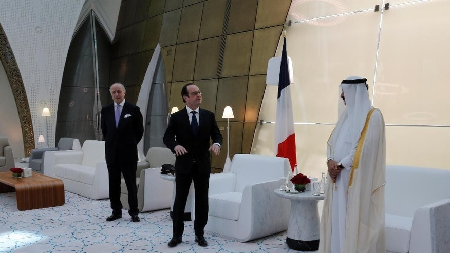 French President Francois Hollande, center,  is greeted by Culture minister of Qatar Dr. Hamad Bin Abdulaziz Al-Kuwari, right, as French foreign minister Laurent Fabius, left, looks on,  at the Doha airport, Qatar, Monday, May 4, 2015. Hollande is seeking to solidify strategic alliances in the Persian Gulf, as he heads to Qatar to sign a 7-billion-euro fighter jet deal and then gets a starring role in a regional summit in Saudi Arabia. (AP Photo/Christophe Ena, Pool)