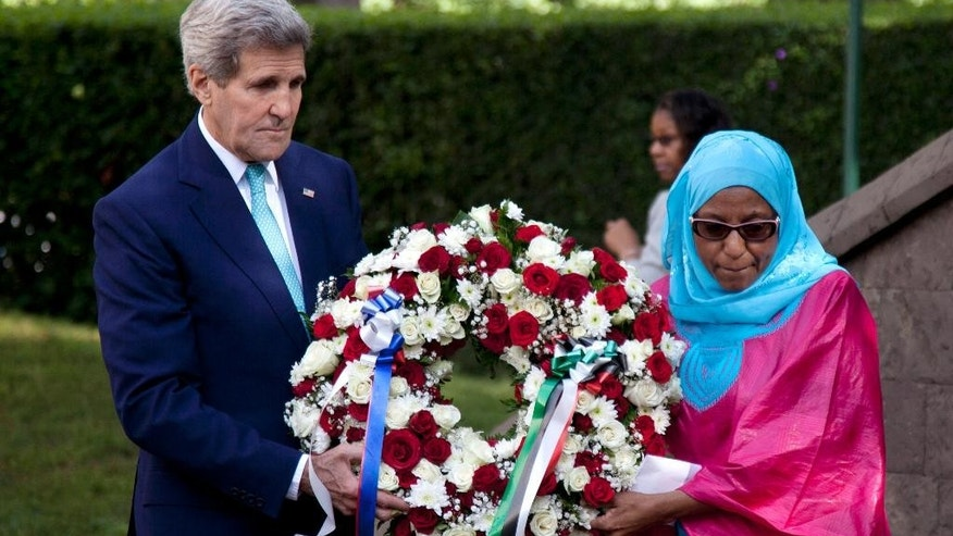 U.S. Secretary of State John Kerry, left, carries a wreath with the help of 1998 bomb survivor, Rukiya Ali,  to lay it at Memorial Park in Nairobi, Kenya, Monday, May  4 , 2015, commemorating the victims of the U.S. embassy bombing, in 1998. U.S. Secretary of State Kerry arrived in the Kenyan capital Nairobi on Sunday afternoon, to assist in the country's fight against terror. (AP Photo/Sayyid Azim)
