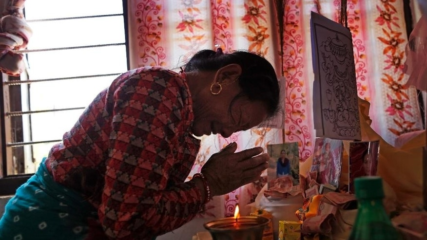 Buddhist follower Mohana Maya Lama, 67, breaks down as she prays over a photo of her daughter who died in last week's massive earthquake at the Nedyon Unphong Thapchyo Monastery in Bidur, Nuwakot District, Nepal, Monday, May 4, 2015. Celebrations of Buddha's birthday in Nepal were muted on Monday, as the country's faithful turned their prayers to loved ones lost in the earthquake and worries that the tragedy may have marked the beginning of a much larger reckoning. (AP Photo/Wally Santana)