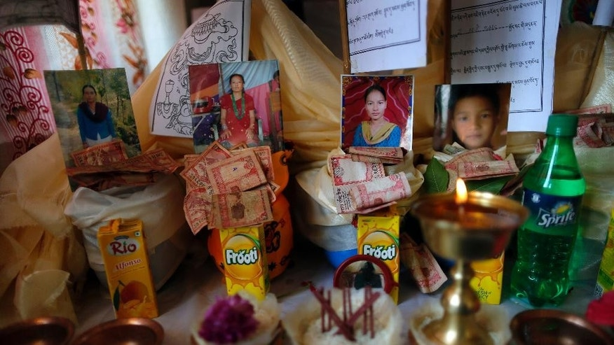 Photos of Buddhists who died in last week's massive earthquake are placed above offerings at the Nedyon Unphong Thapchyo Monastery in Bidur, Nuwakot District, Nepal, Monday, May 4, 2015. Celebrations of Buddha's birthday in Nepal were muted on Monday, as the country's faithful turned their prayers to loved ones lost in the earthquake and worries that the tragedy may have marked the beginning of a much larger reckoning. (AP Photo/Wally Santana)