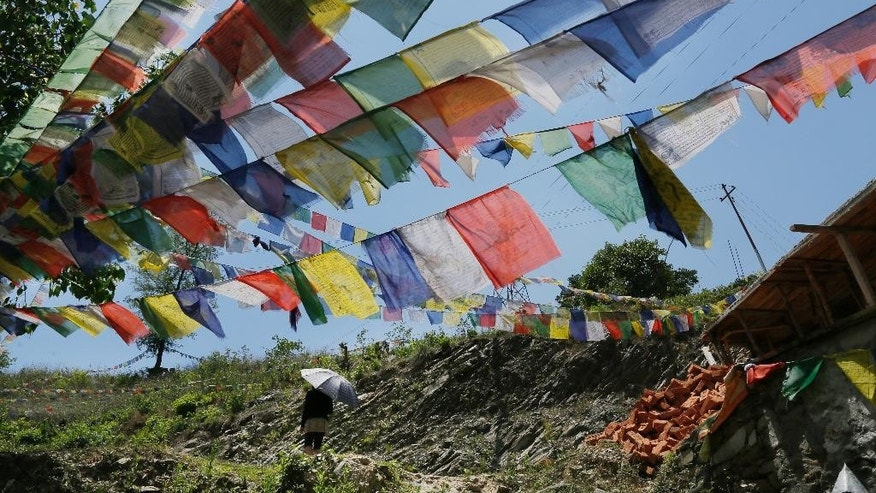 A Buddhist walks under prayer flags after paying her respects for those who died in last week's massive earthquake at the Nedyon Unphong Thapchyo Monastery in Bidur, Nuwakot District, Nepal, Monday, May 4, 2015. Celebrations of Buddha's birthday in Nepal were muted on Monday, as the country's faithful turned their prayers to loved ones lost in the earthquake and worries that the tragedy may have marked the beginning of a much larger reckoning. (AP Photo/Wally Santana)