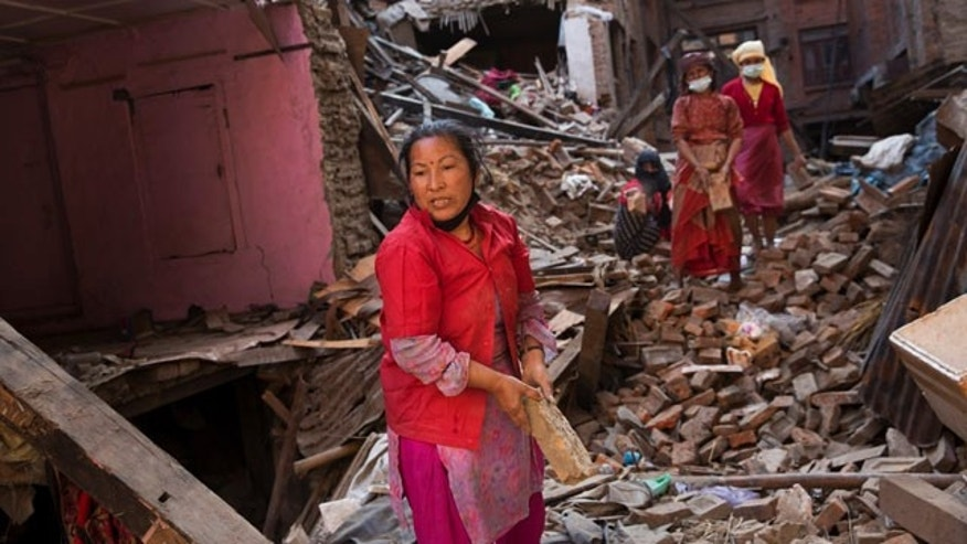 May 3, 2015: Nepalese women remove debris searching their belongings from their house that was destroyed a week ago during the earthquake in Bhaktapur, Nepal. (AP Photo/Bernat Amangue)