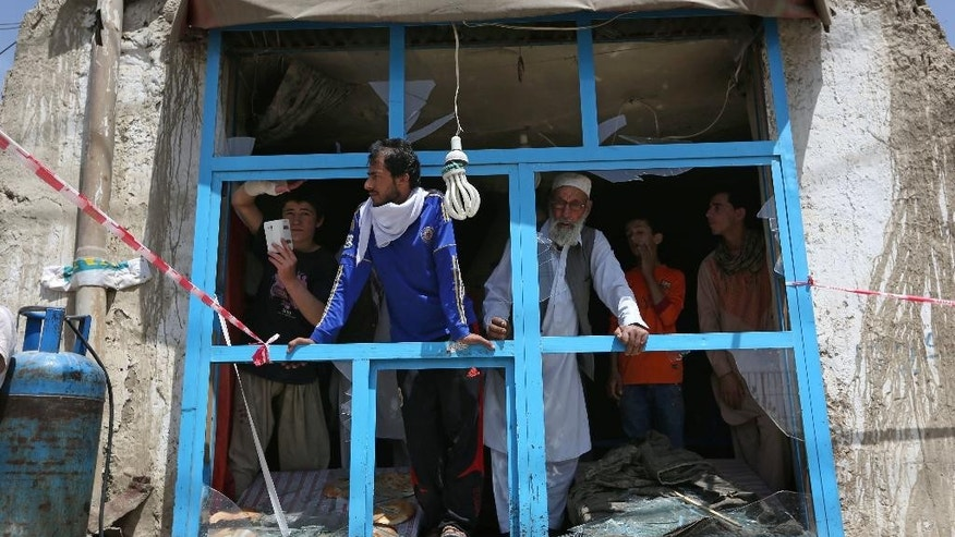 Afghans look out of a damaged shop after a suicide attack in Kabul, Afghanistan, Monday, May 4, 2015. An Afghan official says a suicide bomber struck a minibus carrying government employees in Kabul, killing at least one person and wounding more than a dozen. Interior Ministry spokesman Sediq Sediqqi says the minibus was carrying employees of the attorney general's office when it was attacked early Monday. (AP Photo/Rahmat Gul)