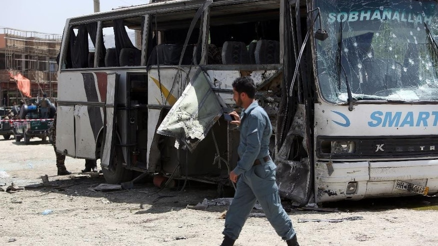 An Afghan security man inspects the site of a suicide attack in Kabul, Afghanistan, Monday, May 4, 2015. An Afghan official says a suicide bomber struck a minibus carrying government employees in Kabul, killing at least one person and wounding more than a dozen. Interior Ministry spokesman Sediq Sediqqi says the minibus was carrying employees of the attorney general's office when it was attacked early Monday. (AP Photo/Rahmat Gul)