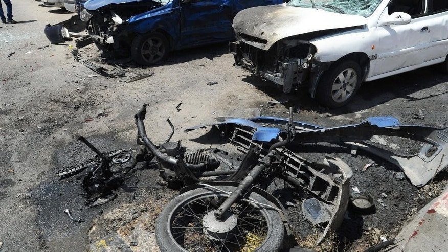 This photo released by the Syrian official news agency SANA, shows damaged cars and a motorcycle after a bombing attack in the Rokn al-Deen neighborhood, Damascus, Syria, Monday, May 4, 2015. A small group of insurgents, including a suicide bomber, carried out the attack in Damascus on Monday targeting a Syrian military logistics and supply facility, militants and activists said. (SANA via AP)