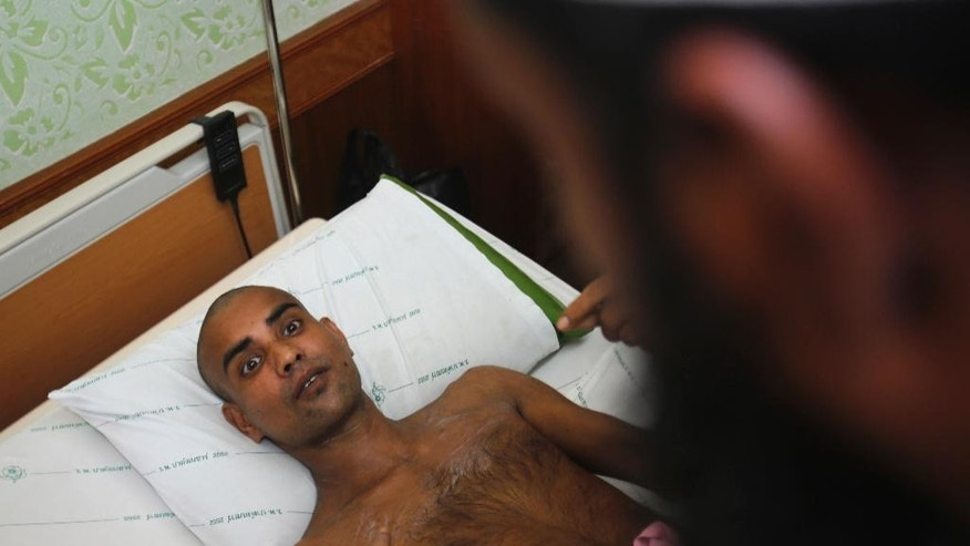 A survivor Tutan Saha, who claimed he was Bangladeshi and was rescued, Friday, May 1, from a detention camp in the Thai-Malaysian border, talks to a Muslim official at a hospital in Padang Besar, Songkhla province, southern Thailand, Monday, May 4, 2015.  Thai police arrested three officials and a Myanmar national in the first real attempt to crack down on a long-existing criminal network that smuggles members of a persecuted Muslim minority of Myanmar into Thailand and keeps them captive under deplorable conditions in the jungles of Thailand.(AP Photo/Sakchai Lalit)