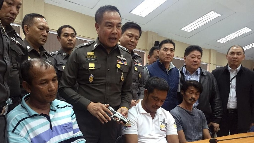 Thailand's national police chief Gen. Somyot Poompanmoung, second from left, holds a pistol seized from one of the three suspects believed to be involved in the human trafficking network after mass graves were discovered on May 1, during a press conference in Hat Yat, Songkhla province, southern Thailand, Monday, May 4, 2015. Police arrested three Thai officials and a Myanmar national in a crackdown on a long-existing criminal network that smuggles persecuted ethnic Muslims from Myanmar into Thailand and holds them captive in camps where scores have died before they can pay ransoms demanded for their freedom. (AP Photo/ ?Thanyarat Doksone)