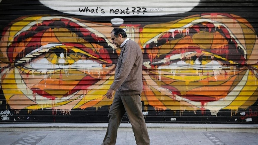 In this photo made on Tuesday, April 29, 2015, a Greek man walks past a graffiti in central Athens. Wednesday May 6 marks five years since Greece voted in its first bailout deal in the face of violent popular protests that left three dead. The day was followed by years of turmoil in which the country tried to overhaul its economy in the midst of a downturn matched in depth and length only by the Great Depression.  (AP Photo/Petros Giannakouris)
