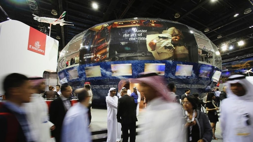 Visitors pass by the Emirates airline booth at the Arabian Travel Market exhibition in Dubai, United Arab Emirates, Tuesday, May 5, 2015. Sheikh Ahmed bin Saeed Al Maktoum, the top boss of the Middle East's biggest airline, Emirates, said he is pressing ahead with a global expansion that includes pursuing additional U.S. routes despite opposition from rivals that accuse the carrier of receiving unfair subsidies. (AP Photo/Kamran Jebreili)
