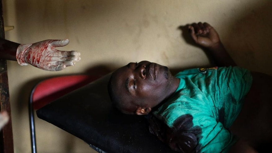 A demonstrator seriously wounded by live ammunition waits for treatment in a small clinic in the Musaga district of Bujumbura, Burundi, Monday May 4, 2015. Anti-government demonstrations resumed in Burundi's capital after a weekend pause as thousands continue to protest the president's decision to seek a third term. (AP Photo/Jerome Delay)