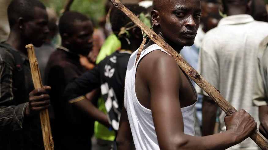 A demonstrator faces police  in the Musaga district of  Bujumbura, Burundi, Tuesday May 5, 2015. The Constitutional court validated  President Pierre Nkurunziza's decision to seek a third term, amid violent street protests.(AP Photo/Jerome Delay)