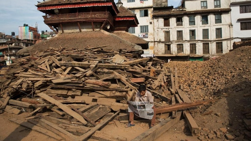 A man reads a newspaper at Basantapur Durbar Square, damaged in the April 25 earthquake in Kathmandu, Nepal, Tuesday, May 5, 2015. Nepal is one of the world's poorest nations, and its economy, largely based on tourism, has been crippled by the earthquake, which left thousands dead. (AP Photo/Bernat Amangue)