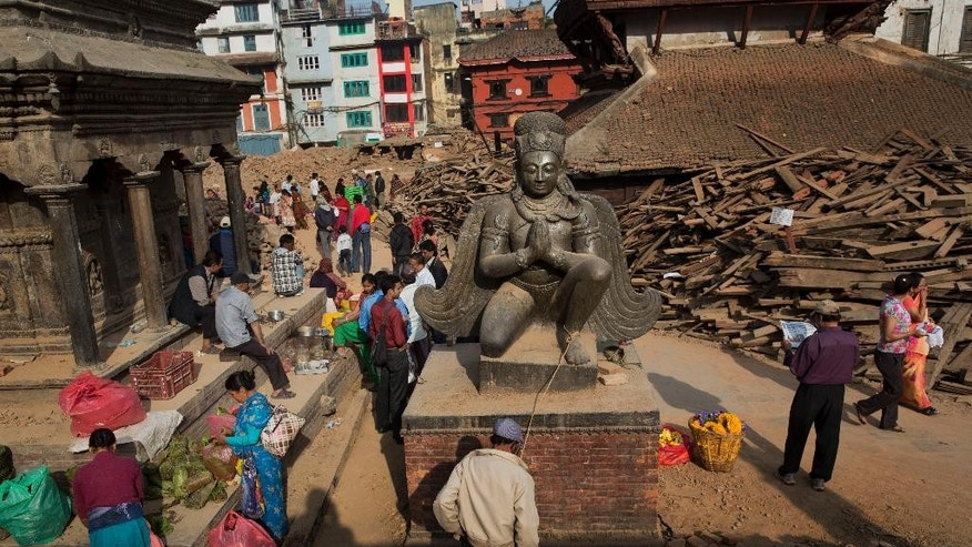 Nepalese gather around Basantapur Durbar Square, damaged in the April 25 earthquake in Kathmandu, Nepal, Tuesday, May 5, 2015. Nepal is one of the world's poorest nations, and its economy, largely based on tourism, has been crippled by the earthquake, which left thousands dead. (AP Photo/Bernat Amangue)
