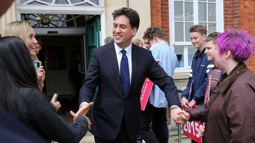 In this Monday, May 4, 2015 photo, Labour Party leader Ed Miliband, center, is greeted by Labour party activists as he leaves Brighton Hove and Sussex Sixth Form College in Brighton, England, on the General Election trail. Miliband's Labour Party is in a virtual dead heat with Prime Minister David Cameron's Conservatives ahead of the vote on Thursday, May 7, 2015. (Chris Radburn/PA via AP) UNITED KINGDOM OUT
