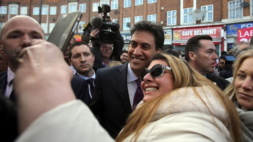 In this Sunday, May 3, 2015 photo, Labour Party leader Ed Miliband, center, poses for a selfie during a campaign visit to Harrow, in Middlesex, England. Miliband's Labour Party is in a virtual dead heat with Prime Minister David Cameron's Conservatives ahead of the vote on Thursday, May 7, 2015. (Chris Radburn/PA via AP) UNITED KINGDOM OUT