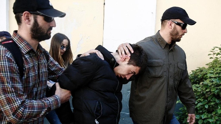 May 5, 2015: Policemen in plain clothes escort a 27-year-old Bulgarian, center, to a magistrate office on charges including murder and defiling the body of his 4-year-old daughter, in Athens, Greece.