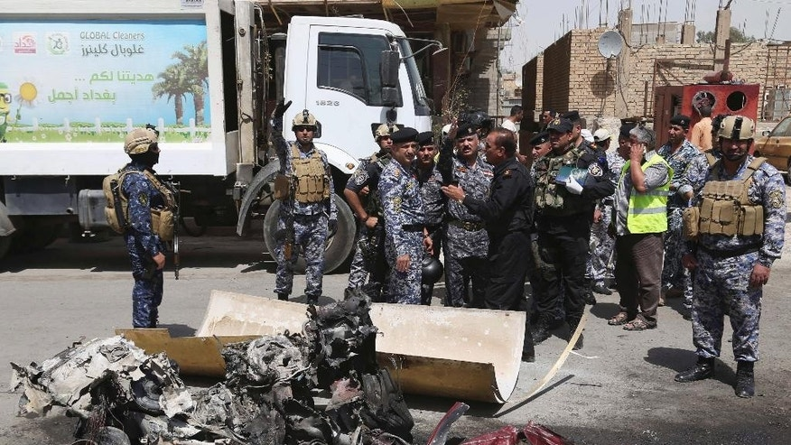 Security forces gather at the scene of a car bomb explosion near Khudairi mosque in Karrada neighborhood, Baghdad, Iraq, Tuesday, May 5, 2015. A car bomb exploded in the central Karrada commercial area killing several people, according to police and medical officials. The area where the car exploded included restaurants, shops and a Sunni mosque. (AP Photo/Khalid Mohammed)