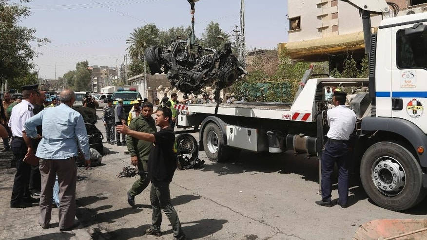 A towing truck lifts a destroyed vehicle at the scene of a car bomb explosion near Khudairi mosque in Karrada neighborhood, Baghdad, Iraq, Tuesday, May 5, 2015. A car bomb exploded in the central Karrada commercial area killing several people, according to police and medical officials. The area where the car exploded included restaurants, shops and a Sunni mosque. (AP Photo/Khalid Mohammed)