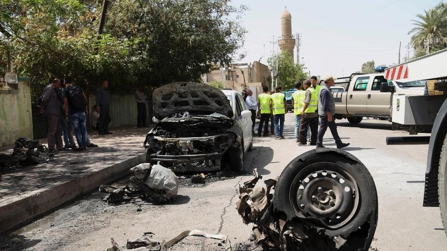 Civilians gather at the scene of a car bomb explosion near Khudairi mosque in Karrada neighborhood, Baghdad, Iraq, Tuesday, May 5, 2015. A car bomb exploded in the central Karrada commercial area killing several people, according to police and medical officials. The area where the car exploded included restaurants, shops and a Sunni mosque. (AP Photo/Khalid Mohammed)