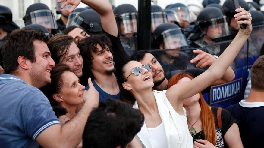 Protestors take a selfie in front of a police cordon during a demonstration in front of the Government building in Skopje Macedonia, on Tuesday, May 5, 2015. Macedonia's opposition leader has accused the country's prime minister of attempting to cover up the 2011 death of a 22-year-old who was beaten by police during post-election celebrations. More than 1,000 people gathered later Tuesday in front of the government building to protest the murder of the young conservative supporter. (AP Photo/Boris Grdanoski)