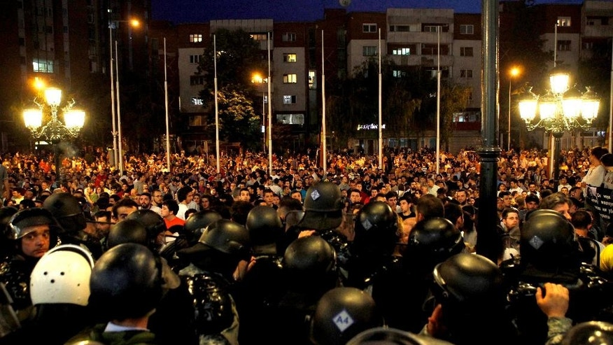 Police block protestors at the entrance of the Government building during a protest in Skopje Macedonia, on Tuesday, May 5, 2015. Macedonia's opposition leader has accused the country's prime minister of attempting to cover up the 2011 death of a 22-year-old who was beaten by police during post-election celebrations. More than 1,000 people gathered later Tuesday in front of the government building to protest the murder of the young conservative supporter. (AP Photo/Boris Grdanoski)