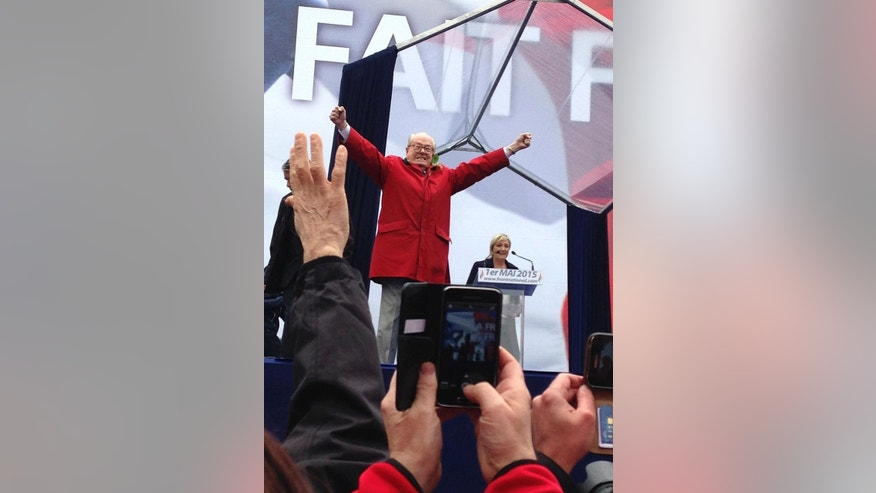 In this May 1 2015 photo, Jean-Marie le Pen, former head of far-right party National Front, takes the stage during the party rally while his daughter and current leader Marine Le Pen, right behind, looks on, in Paris, France. The party's executive bureau was to meet Monday to decide possible sanctions against Jean-Marie Le Pen over his anti-Semitic remarks, amid a high-stakes family feud. His daughter Marine Le Pen — the current party leader — and other rising stars within the party want to shut him up. (AP Photo/Elaine Ganley)
