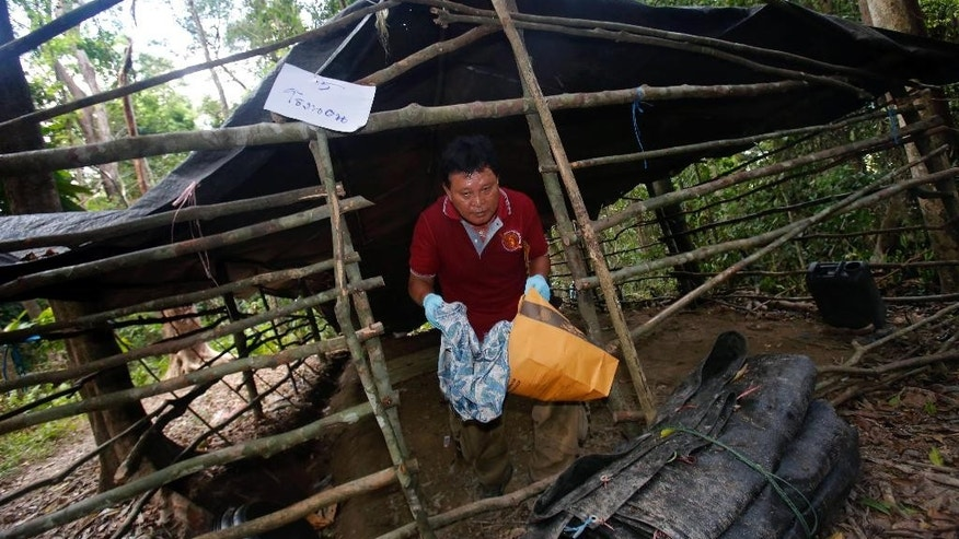 A forensic police officer collects items left at an abandoned migrant camp on Khao Kaew Mountain near the Thai-Malaysian border in Padang Besar, Songkhla province, southern Thailand, Tuesday, May 5, 2015. Police have found a recently abandoned camp on a forested hillside in southern Thailand believed to have held human trafficking victims, days after the grim discovery of 26 bodies at a separate location exposed a thriving human smuggling network. (AP Photo/Sakchai Lalit)