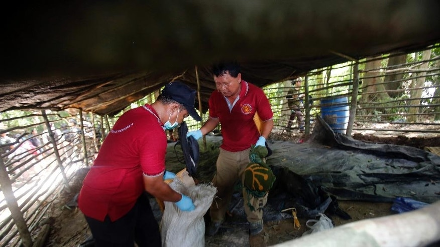 Forensic police officers collect items left at an abandoned migrant camp on Khao Kaew Mountain near the Thai-Malaysian border in Padang Besar, Songkhla province, southern Thailand, Tuesday, May 5, 2015. Police have found a recently abandoned camp on a forested hillside in southern Thailand believed to have held human trafficking victims, days after the grim discovery of 26 bodies at a separate location exposed a thriving human smuggling network. (AP Photo/Sakchai Lalit)