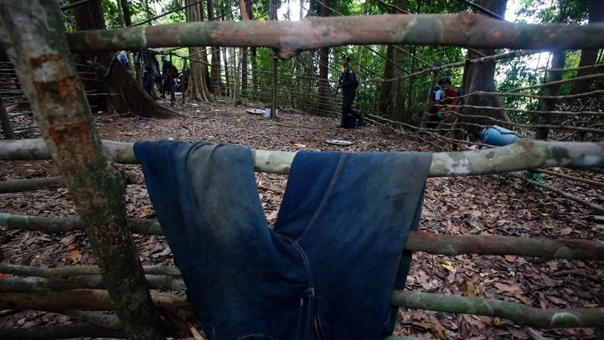 A Thai Border patrol police officer walks behind a pair of jeans left at abandoned migrant camp on Khao Kaew Mountain near the Thai-Malaysian border in Padang Besar, Songkhla province, southern Thailand, Tuesday, May 5, 2015. Police have found a recently abandoned camp on a forested hillside in southern Thailand believed to have held human trafficking victims, days after the grim discovery of 26 bodies at a separate location exposed a thriving human smuggling network.(AP Photo/Sakchai Lalit)