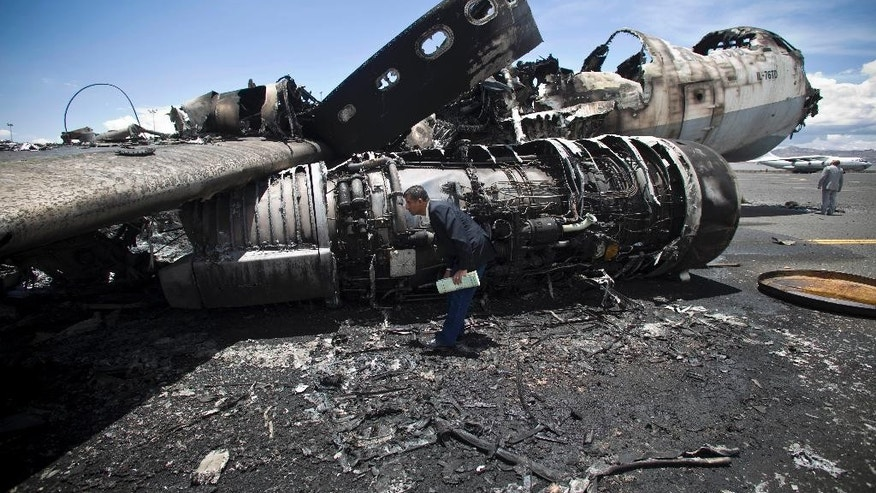 An airport official looks at the wreckage of a military transport aircraft destroyed by Saudi-led airstrikes, at the Sanaa International airport, in Yemen, Tuesday, May 5, 2015. A Saudi-led coalition continues to bomb Shiite rebels also known as Houthis and allied forces across the country. The airstrikes campaign, which began on March 26, and the ground fighting have killed hundreds and displaced at least 300,000 Yemenis.  (AP Photo/Hani Mohammed)