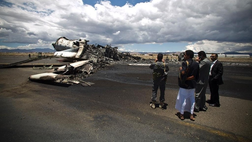 Airport officials look at the wreckage of a military transport aircraft destroyed by Saudi-led airstrikes, at the Sanaa International airport, in Yemen, Tuesday, May 5, 2015. A Saudi-led coalition continues to bomb Shiite rebels also known as Houthis and allied forces across the country. The airstrikes campaign, which began on March 26, and the ground fighting have killed hundreds and displaced at least 300,000 Yemenis.  (AP Photo/Hani Mohammed)