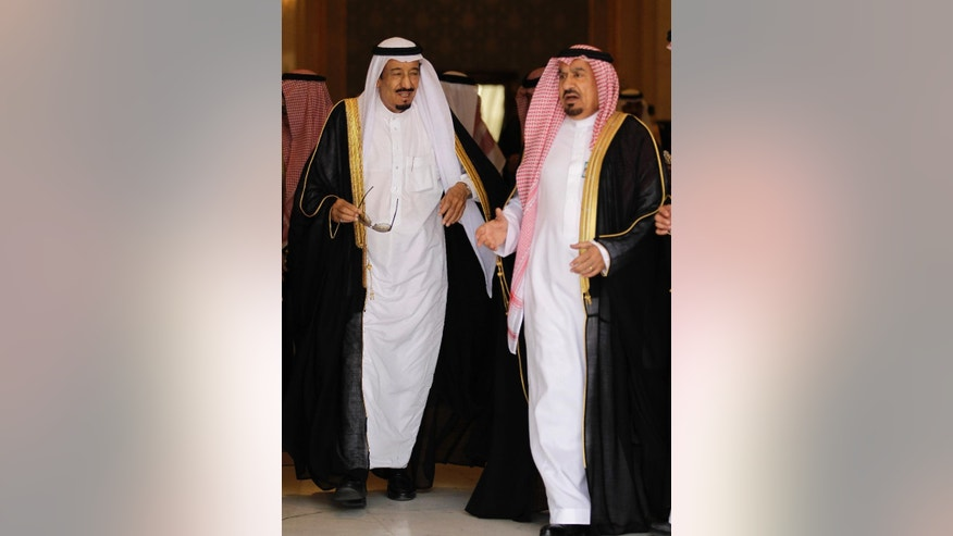 In this Monday, May 14, 2012 photo, the then Saudi Defense Minister Prince Salman bin Abdel-Aziz, left, and Saudi chief of protocol Mohammed al-Tobayshi arrive to welcome Arab leaders for the Arab Summit at the airbase in Riyadh, Saudi Arabia. Saudi King Salman has fired the chief of royal protocol after he was caught on camera slapping a photographer. The official Saudi Press Agency and local media reported Tuesday, May 5, 2015 that al-Tobayshi was replaced by Khalid al-Abbad, though no reason was given for the change. (AP Photo/Hassan Ammar)
