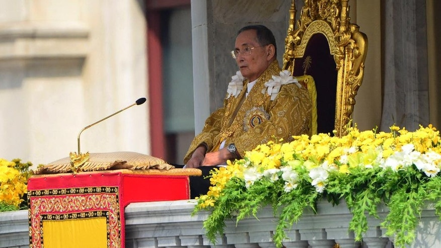 "FILE - In this Dec. 5, 2012 file photo, Thai King Bhumibol Adulyadej appears to address a crowd from the balcony at the Anantha Samakhom Throne Hall in Bangkok, Thailand, during his 85th birthday celebration. Thailand's 87-year-old monarch made a rare public appearance Tuesday, May 5, 2015 to mark the 65th anniversary celebrating his coronation. Thais lined the roads of Bangkok's historic district chanting, ""Long Live the King!"" as the revered King Bhumibol was driven from the hospital, where he has taken up residence, to the Grand Palace. (AP Photo/Sakchai Lalit, File)"
