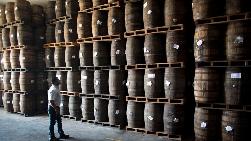 In this Thursday, March 26, 2015 photo, Jhorgen Romero, Head of Processing and Aging at Santa Teresa looks at the barrels filled with rum at the Santa Teresa rum factory in La Victoria, Aragua State, Venezuela. The fall in international oil prices and the consequent shortage of foreign exchange seriously affects Venezuela's economy, heavily dependent on imports, but for some domestic producers like rum manufacturers it's an opportunity to increase production and meet growing sales inside and outside the country. (AP Photo/Ariana Cubillos)