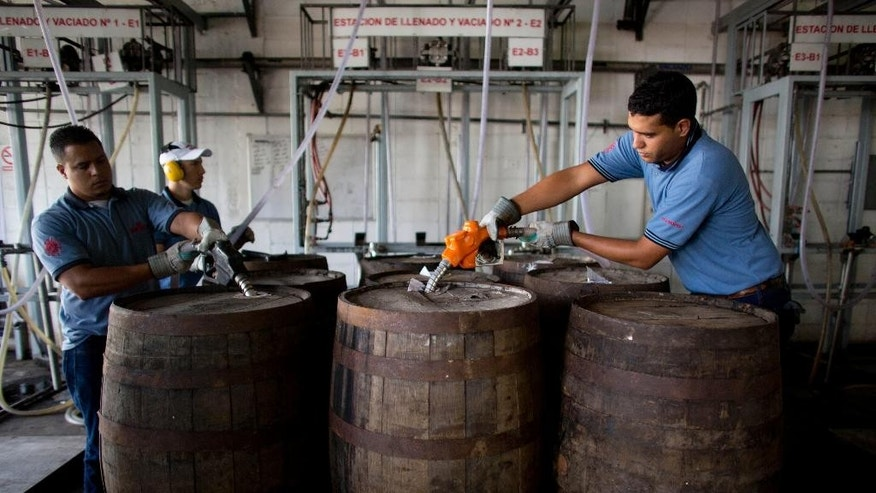 In this Thursday, March 26, 2015 photo, workers fill barrels with rum at the Santa Teresa factory in La Victoria, Aragua State, Venezuela. Venezuela long was Latin America's biggest market for whisky, which for decades has been recognized as a status symbol. Venezuelans commonly throw back whisky at baseball games and arena concerts, and even working-class families seek out fine Scotch for special events like weddings. But the country's economic collapse has forced a rum revival. (AP Photo/Ariana Cubillos)