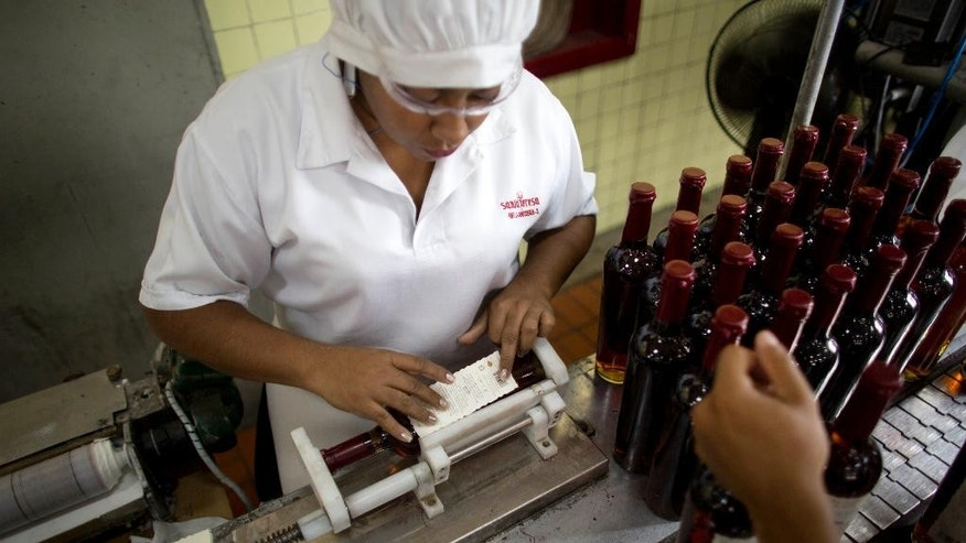 In this Thursday, March 26, 2015 photo, workers stick labels on rum bottles at the Santa Teresa rum factory in La Victoria, Aragua State, Venezuela. With inflation running above 60 percent, Venezuelans' money no longer goes as far, putting whiskey beyond reach for many. Such economic downturns often have prompted a boost in domestic spirits. (AP Photo/Ariana Cubillos)
