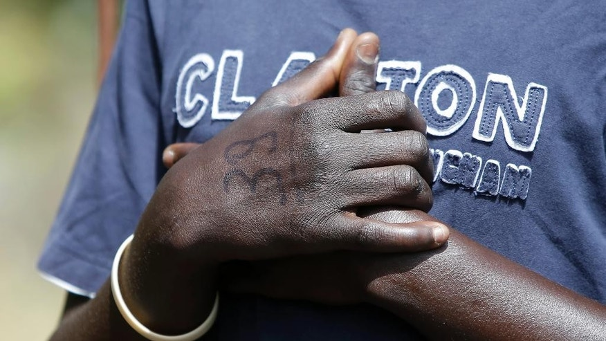 Baboucar Lowe, a 17-year-old migrant from Gambia, holds his hands, bearing an Italian authorities identification number, during an interview with the Associated Press, in Nicolosi, Sicily, southern Italy, Wednesday, May 6, 2015. Baboucar nearly lost his life when the dinghy he was on deflated within sight of a rescue ship. He recounted the moment when more than 100 people aboard the deflating dinghy tried to climb aboard lines thrown by the Maltese freighter Zeran and dozens fell into the sea, drowning. (AP Photo/Antonio Calanni)