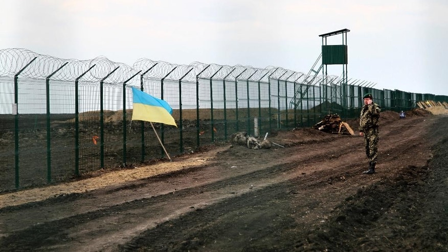 In this photo taken on Saturday, April 18, 2015, a Ukrainian border guard officer speaks on a phone near a national flag attached to the fence on the Ukrainian-Russian border near Hoptivka, Kharkiv region, eastern Ukraine. The flimsy, razor wire-topped fences popping up along bare expanses of Ukraine's eastern frontier are the first line of defense against a much-feared Russian invasion. (AP Photo/Inna Varenytsia)