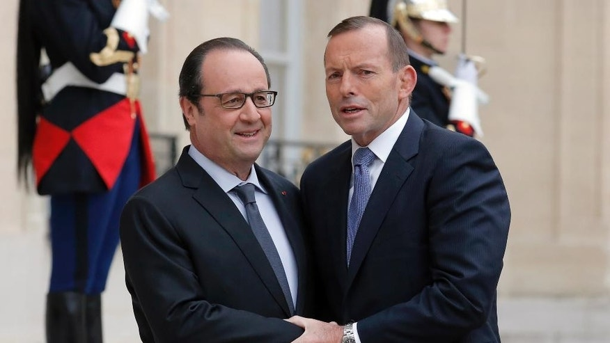 FILE - In this April 27, 2015 file photo, Australian Prime Minister Tony Abbott, right, is greeted by French President Francois Hollande upon his arrival for their meeting at the Elysee Palace in Paris, France. Abbott on Wednesday, May 6, brushed off controversy over his office's treatment of the gay partner of the Australian ambassador to France. Ambassador Stephen Brady offered to resign after a disagreement involving Abbott's reception at Le Bourget Airport in Paris last month, Fairfax Media reported. (AP Photo/Francois Mori, File)