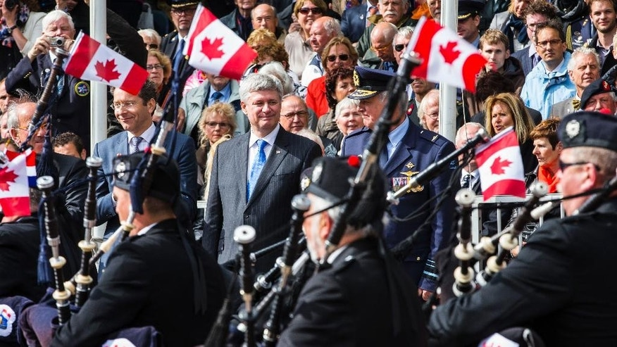 Canadian Prime Minister Stephen Harper, center, watches a parade in Wageningen, Netherlands, Tuesday May 5, 2015, marking the 70th anniversary of the surrender of Nazi forces on May 5, 1945. A week of celebrations and remembrances marks the 70th anniversary of the liberation of the Netherlands at the end of World War II. (AP Photo/Vincent Jannink)