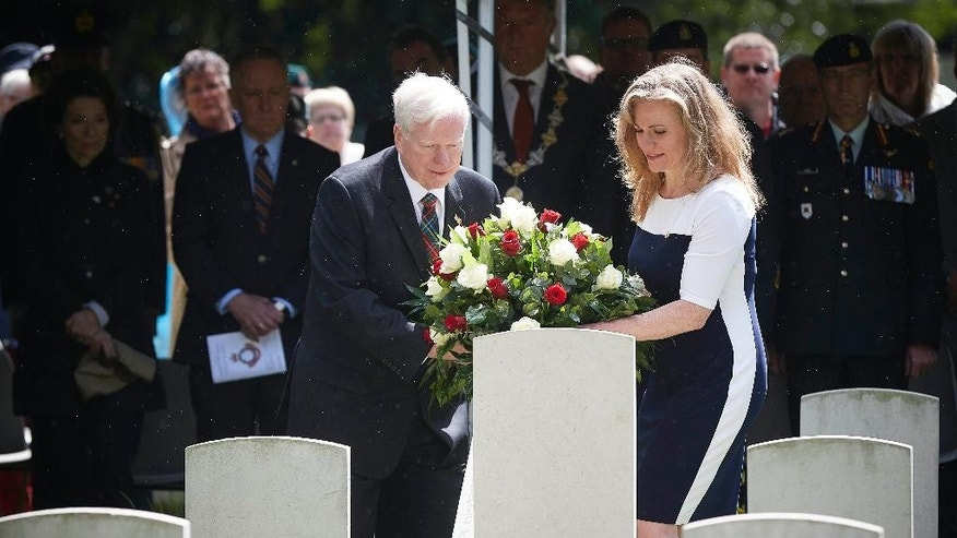 Relatives Glen Laubenstein, left, and his daughter Sarah Penton, right, place flowers near the grave of Canadian Private Albert Laubenstein during a ceremony at the Canadian War Cemetery in Bergen op Zoom, south-west Netherlands, Wednesday, May 6, 2015. Laubenstein has found a final resting place 70 years after he was killed during the Allied advance through the Netherlands in the closing months of World War II. Laubenstein was buried with military honors. His remains were found only in June last year and his burial was one of the highlights of a week of remembrances and celebrations to mark Canada's part in the liberation of the Netherlands. (AP Photo/Phil Nijhuis)