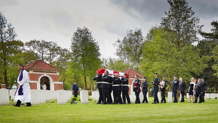 Relatives Glen Laubenstein, fiftht right, and his daughter Sarah Penton, fourth right, follow a coffin bearing the remains of Canadian Private Albert Laubenstein to the grave during a ceremony at the Canadian War Cemetery in Bergen op Zoom, south-west Netherlands, Wednesday, May 6, 2015. Laubenstein has found a final resting place 70 years after he was killed during the Allied advance through the Netherlands in the closing months of World War II. Laubenstein was buried with military honors. His remains were found only in June last year and his burial was one of the highlights of a week of remembrances and celebrations to mark Canada's part in the liberation of the Netherlands. (AP Photo/Phil Nijhuis)