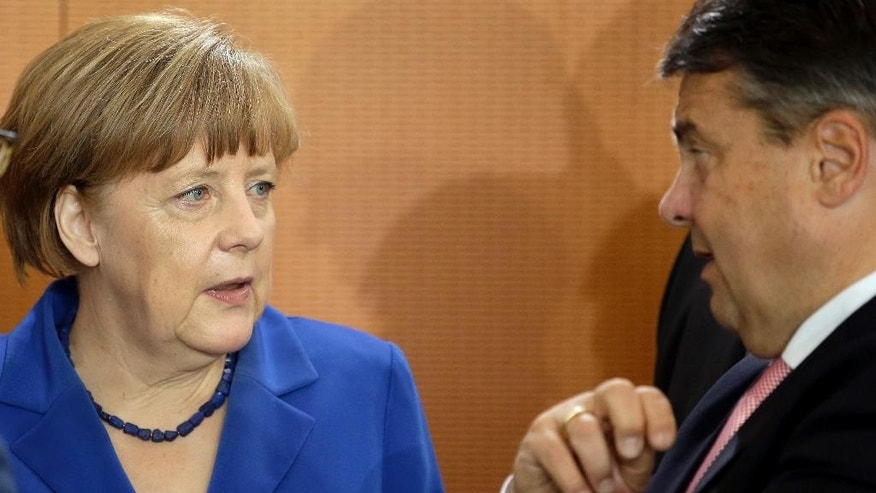 German Chancellor Angela Merkel, left, and Vice Chancellor and Economy Minister Sigmar Gabriel, right, talk as they arrive for the weekly cabinet meeting at the chancellery in Berlin, Germany, Wednesday, May 6, 2015. (AP Photo/Michael Sohn)