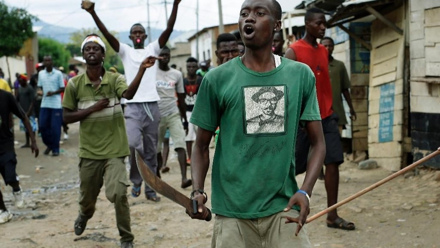 Demonstrators, some carrying machetes, shout as police are dismantling a barricade in the Kanyosha district of Bujumbura, Burundi, Wednesday May 6, 2015. Anti-government demonstrations continue Wednesday and protesters regularly set road blocks in Burundi's capital after the constitutional court validated  President Pierre Nkurunziza's decision to seek a third term in office.(AP Photo/Jerome Delay)