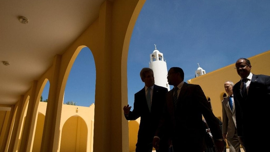 "Silhouetted in the shadows of the Salman Mosque,  U.S. Secretary of State John Kerry, left, accompanied by, Djibouti Minister of Muslim Affairs and Culture Aden Hassan Aden, second from left, U.S. Ambassador to Djibouti Tom Kelly, second from right, and Foreign Minister Mahamoud Ali Youssouf, right, departs the Salman Mosque after meeting with youth, Wednesday, May 6, 2015, in Dijbouti, Dijbouti.  Kerry said Wednesday he intends to discuss with Saudi Arabian officials how to implement a ""humanitarian pause"" in Yemen's civil war, citing increased shortages of food, fuel and medicine that are adding to a crisis that has already caused some thousands of people to flee to neighboring countries. (AP Photo/Andrew Harnik, Pool)"