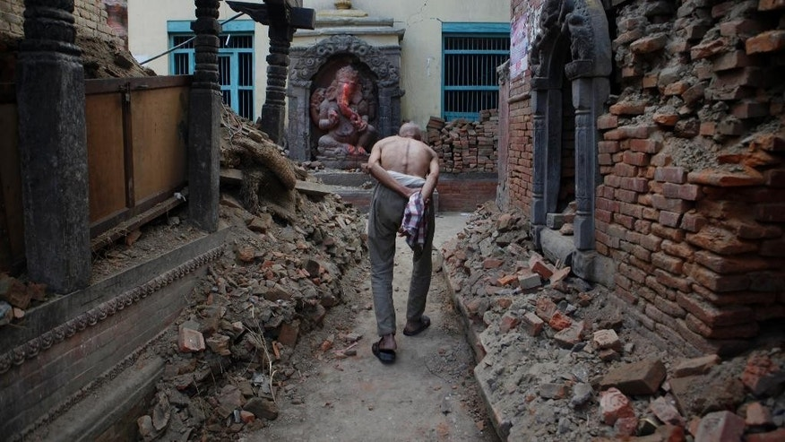 An elderly Nepalese walks past a damaged temple performing rituals to end the mourning period of a family member who died in the April 25 earthquake, in Bhaktapur, Nepal, Wednesday, May 6, 2015. The April 25 earthquake killed thousands and injured many more as it flattened mountain villages and destroyed buildings and archaeological sites in Kathmandu. (AP Photo/Niranjan Shrestha)