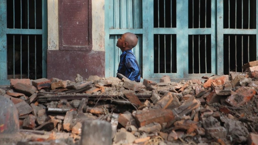 A Nepalese boy, who lost a family member to the April 25 earthquake, walks past debris as he performs rituals to end the mourning period, in Bhaktapur, Nepal, Wednesday, May 6, 2015. The April 25 earthquake killed thousands and injured many more as it flattened mountain villages and destroyed buildings and archaeological sites in Kathmandu. (AP Photo/Niranjan Shrestha)