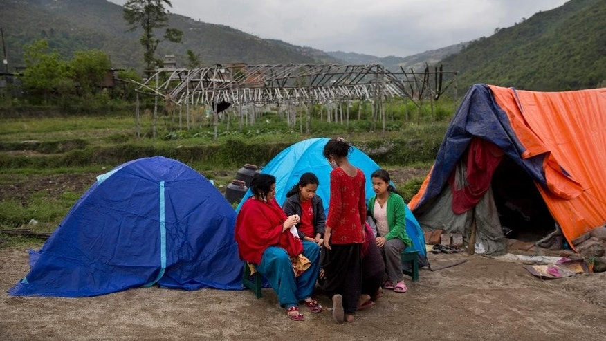 FILE - In this April 29, 2015 file photo, earthquake-affected Nepalese villagers gather by tents where they have taken shelter in Sakhu, on the outskirts of Kathmandu, Nepal. Sakhu is where the side streets are choked with chest-high hills of bricks, concrete and wood after the massive earthquake that hit Nepal on April 25. (AP Photo/Bernat Amangue, File)