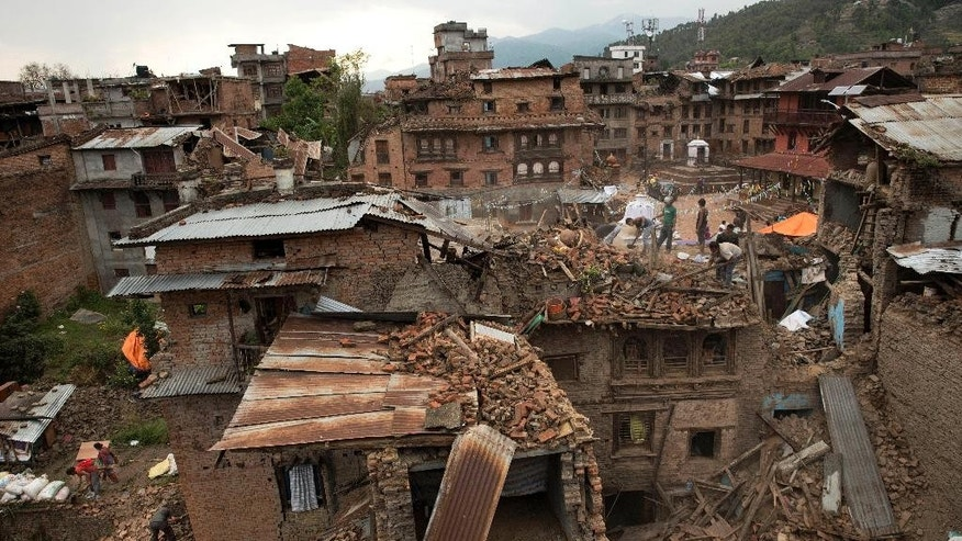 FILE - In this April 29, 2015 file photo, people clear the debris from damage caused by an earthquake in Sakhu, on the outskirts of Kathmandu, Nepal. Sakhu is where the side streets are choked with chest-high hills of bricks, concrete and wood after the massive earthquake that hit Nepal on April 25. (AP Photo/Bernat Amangue, File)
